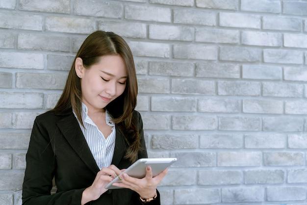 Asiatische geschäftsfrau, die tablette verwendet, um über verkaufs- und marketing-plan zu arbeiten