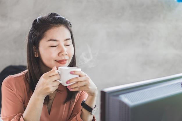 Asiatische geschäftsfrau, die tasse kaffee riecht