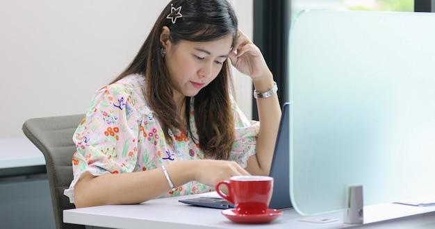 Asiatische geschäftsfrau, die über die arbeit ernst ist und notizbuch verwendet