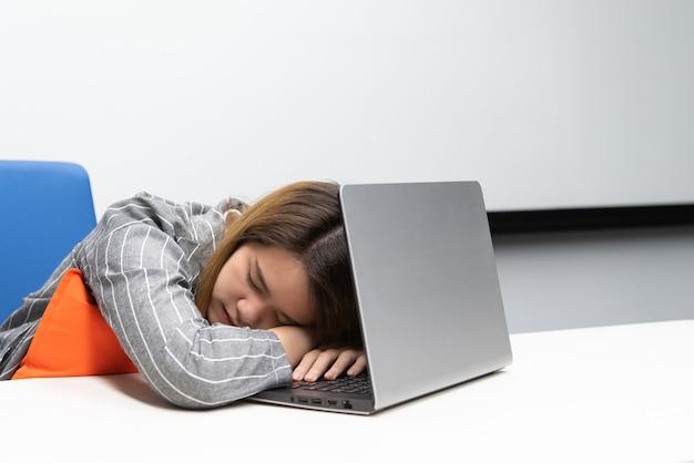 Asiatische geschäftsfrau, die über einem laptop in einem büroraum schläft