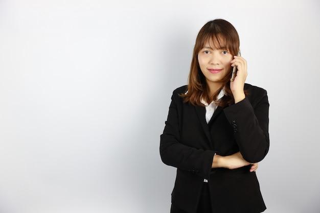 Asiatische geschäftsfrau, die überzeugtes gesicht des handys auf weiß verwendet