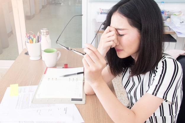 Asiatische geschäftsfrau, die unter den chronischen täglichen kopfschmerzen, ernennend zu einer medizinischen beratung leidet