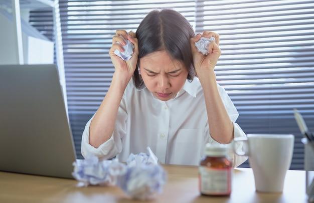 Asiatische geschäftsfrau, die unter starken kopfschmerzen oder migräne wegen der harten arbeit und des druckes leidet.