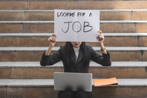 Asiatische geschäftsfrau, die versucht, job zu finden und papierzeichen zeigt, um anderen leuten zu sagen, dass sie nach einem job sucht.