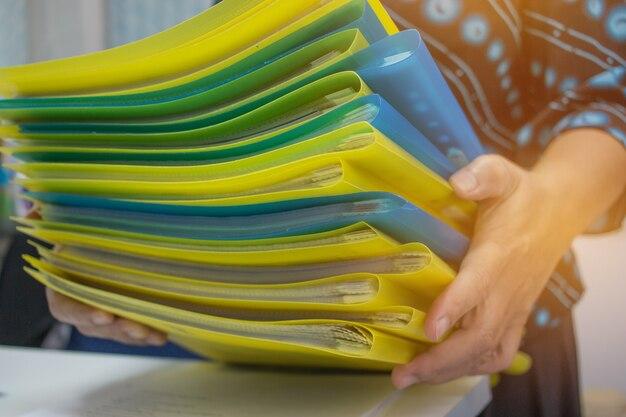 Asiatische geschäftsfrau, die viele dokumente hält stapel ordner im büro für jahresberichtdateien