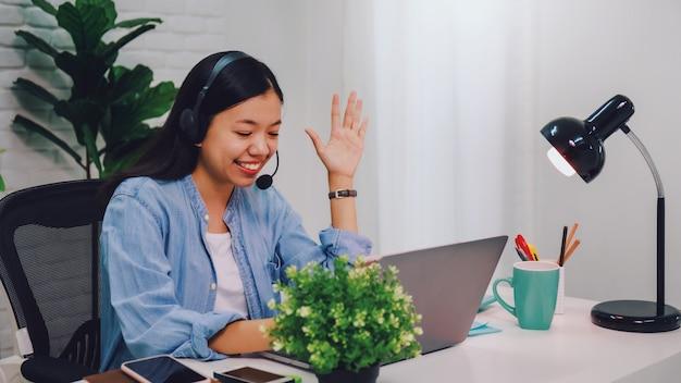Asiatische geschäftsfrau, die von zu hause mit laptop arbeitet