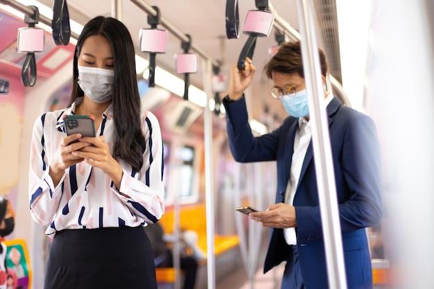 Asiatische geschäftsfrau, die während der covid-19-pandemie beim pendeln mit öffentlichen verkehrsmitteln gesichtsmasken trägt