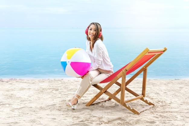 Asiatische geschäftsfrau, die wasserball bei der anwendung von den kopfhörern sitzen im strandstuhl auf strand hält