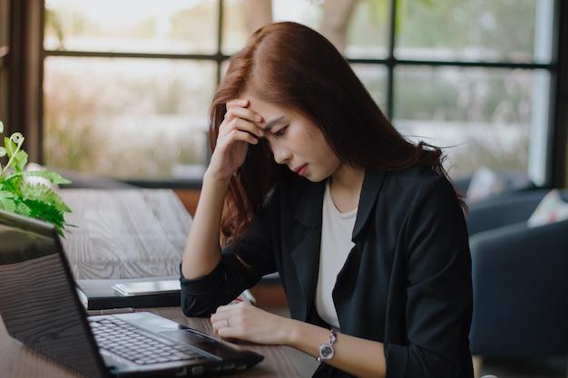 Asiatische geschäftsfrau ernst über die arbeit erledigt bis die kopfschmerzen