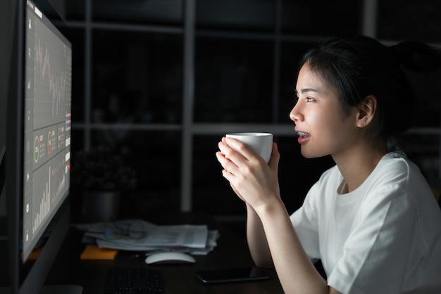 Asiatische geschäftsfrau händler suchen und trinken kaffee mit graphen analyse kerze linie auf tisch im nachtbüro, diagramme auf dem bildschirm. börsenkonzept