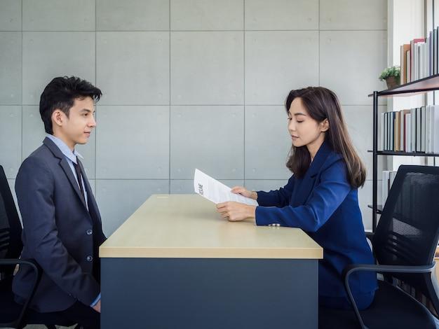 Asiatische geschäftsfrau, hr-überprüfung lebenslauf des jungen asiatischen geschäftsmannes im anzug im amt