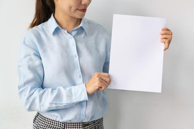 Asiatische geschäftsfrau im blauen hemd hält ein leeres blatt papier in den händen lokalisiert über weiß