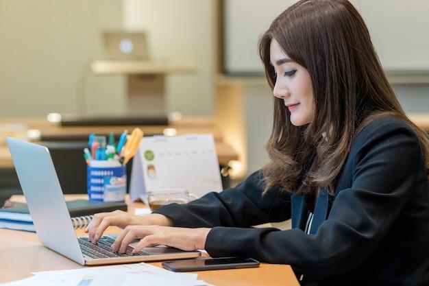 Asiatische geschäftsfrau im gesellschaftsanzug, der mit computerlaptop arbeitet