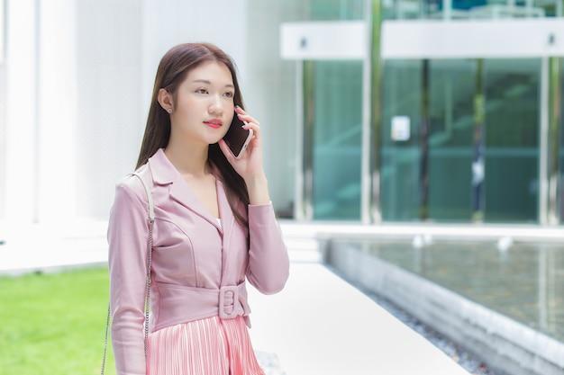 Asiatische geschäftsfrau im rosafarbenen kleid ruft ernsthaft mit jemandem im gebäude an?