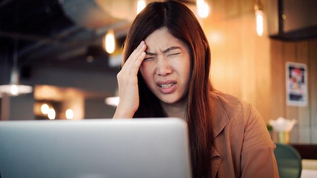 Asiatische geschäftsfrau in der zufälligen klage, die mit computer im druckgefühl an zusammenarbeitenden s arbeitet