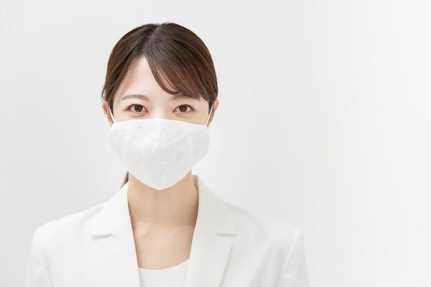 Asiatische geschäftsfrau in einem weißen anzug, der eine maske trägt