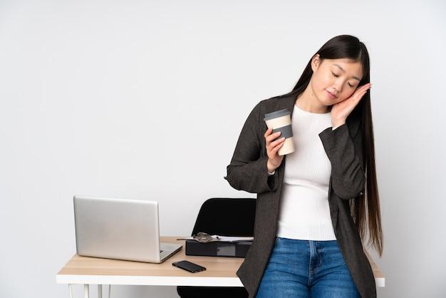 Asiatische geschäftsfrau in ihrem arbeitsplatz auf weißer wand, die schlafgeste in entzückendem ausdruck macht
