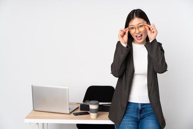 Asiatische geschäftsfrau in ihrem arbeitsplatz auf weißer wand mit brille und überrascht
