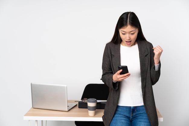 Asiatische geschäftsfrau in ihrem arbeitsplatz auf weißer wand überrascht und eine nachricht sendend