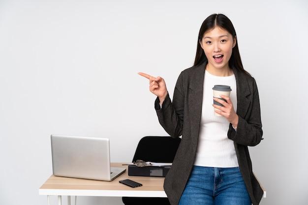 Asiatische geschäftsfrau in ihrem arbeitsplatz auf weißer wand überrascht und zeigende seite