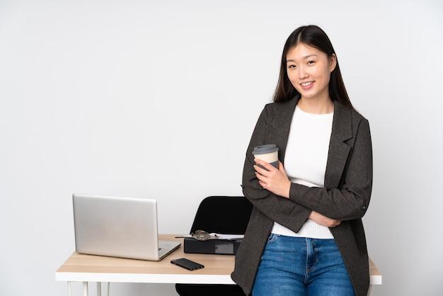 Asiatische geschäftsfrau in ihrem arbeitsplatz lokalisiert auf weißer wand mit verschränkten armen und nach vorne schauend