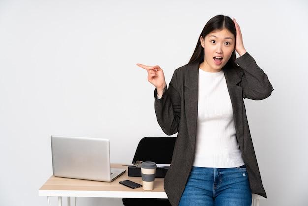 Asiatische geschäftsfrau in ihrem arbeitsplatz lokalisiert auf weißer wand überrascht und finger zur seite zeigend