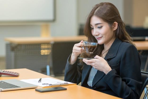 Asiatische geschäftsfrau in trinkendem kaffee der formalen klage