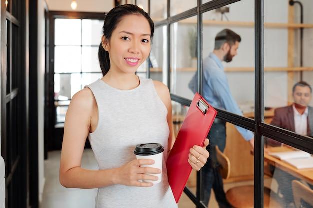 Asiatische geschäftsfrau kommt zur arbeit