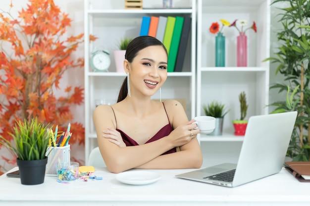 Asiatische geschäftsfrau machen eine kaffeepause, nachdem sie an der laptop-computer auf schreibtisch gearbeitet hat