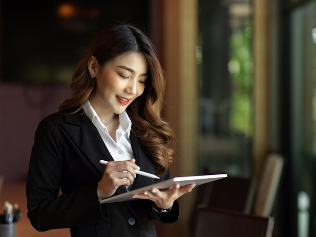Asiatische geschäftsfrau mit digitalem tablet-anzug in ihren händen im büro, die online über tablet arbeitet