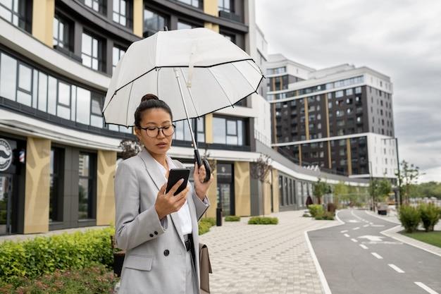Asiatische geschäftsfrau mit regenschirm, die im smartphone scrollt