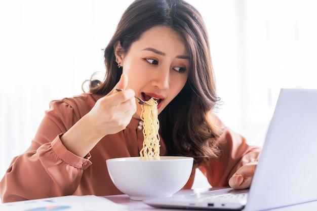 Asiatische geschäftsfrau muss während der arbeit nudeln essen