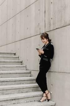 Asiatische geschäftsfrau plaudert und steht auf treppe