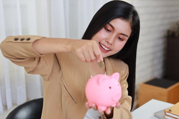 Asiatische geschäftsfrau sitzt und steckt münze ins sparschwein