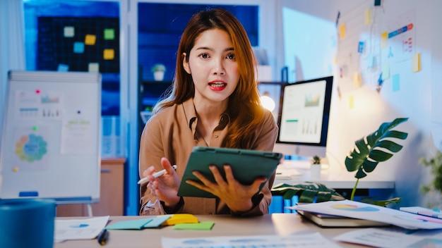 Asiatische geschäftsfrau soziale distanzierung in neuer normalität für die virusprävention, die sich während der arbeit in der büronacht die kamerapräsentation für den kollegen über den plan im videoanruf ansieht.