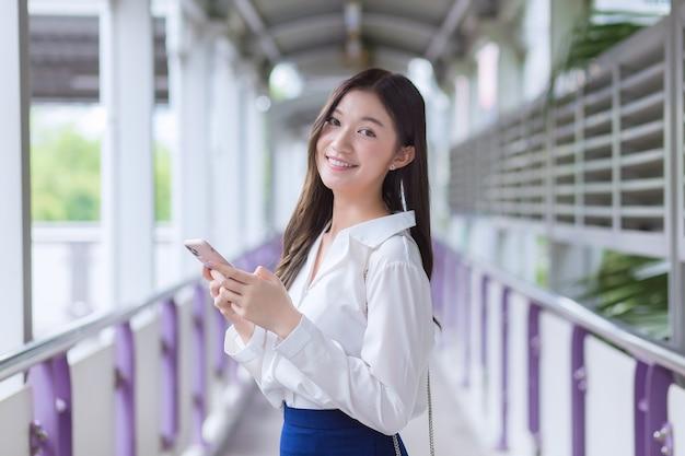 Asiatische geschäftsfrau steht auf der überführung des skytrain in der stadt, während sie ihr smartphone benutzt