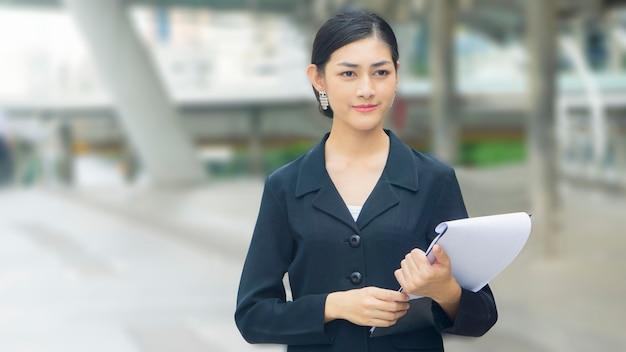 Asiatische geschäftsfrau steht mit überzeugter veröffentlichungs- und darstellungspapierdatei öffentlichen raum am im freien