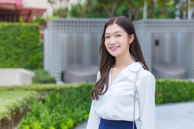 Asiatische geschäftsfrau trägt ein weißes hemd und lächelt glücklich