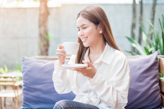 Asiatische geschäftsfrau trinkt kaffee morgens an der kaffeestube