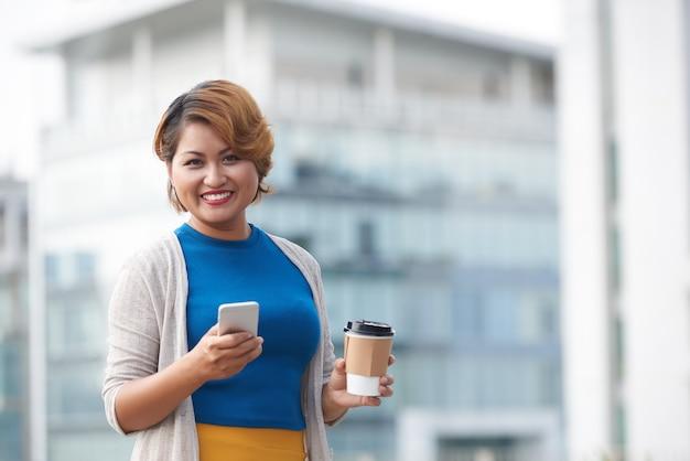 Asiatische geschäftsfrau trinkt kaffee zum mitnehmen