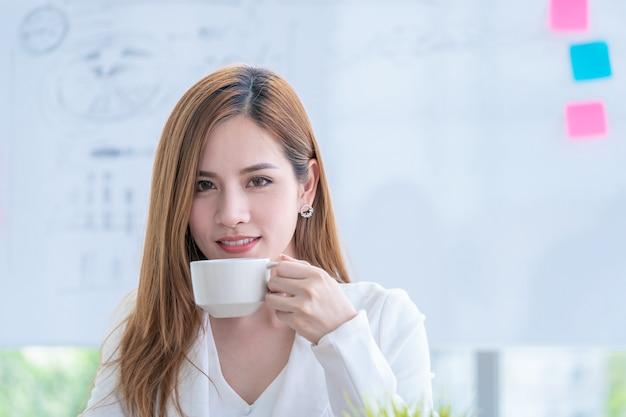 Asiatische geschäftsfrau überprüft den bericht beim trinken des kaffees