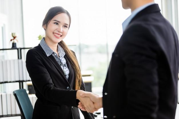 Asiatische geschäftsfrau und geschäftsmann, die hände am im büroraum rüttelt, nachdem der vertrag unterzeichnet wird, oder händedruckgrußabkommen, geschäft drückten das ermutigte vertrauen und erfolgreiches konzept aus