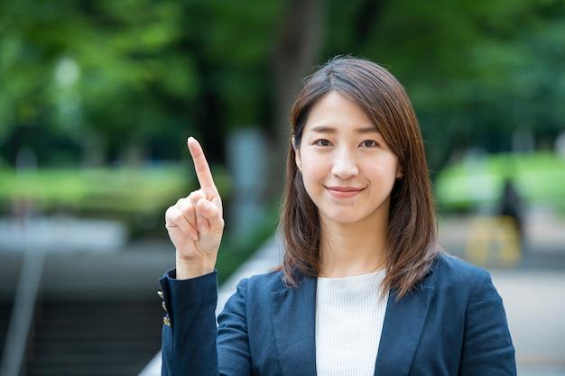 Asiatische geschäftsfrau zeigt nach oben
