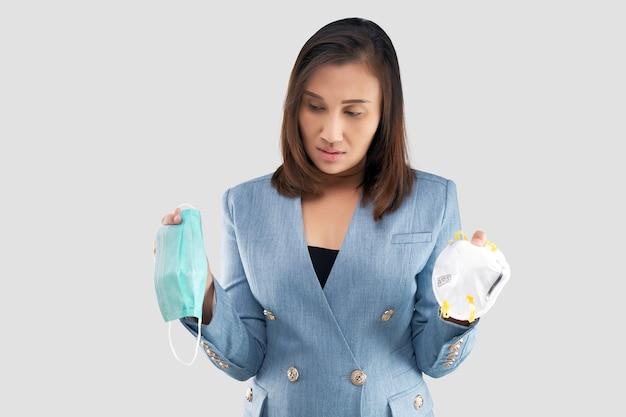 Asiatische geschäftsfrau zögern, eine gesundheitsmaske auf dem grauen hintergrund zu wählen