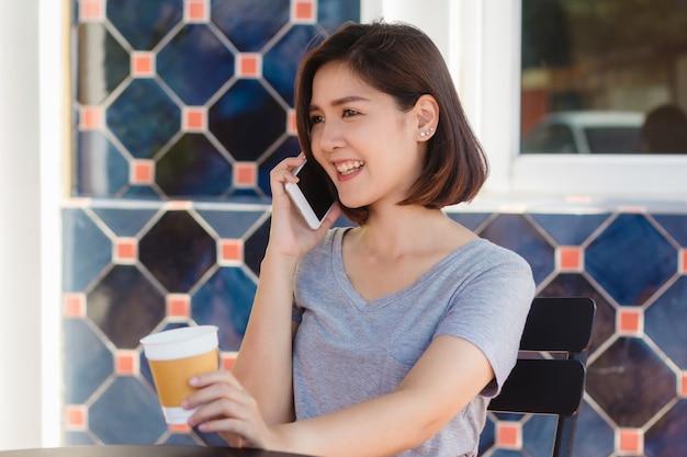 Asiatische geschäftsfrauen des glücklichen lächelns, die den unterhaltungshandy sitzen im café und im halten einer schale coffe verwenden