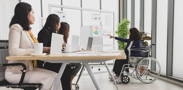 Asiatische geschäftsfrauen, die auf dem tisch mit laptops vor dem hören von handicap sitzen geschäftsfrau, die auf rollstuhl sitzt und diagramme und diagramme auf dem brett im büro präsentiert.