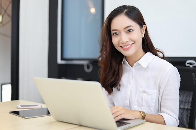 Asiatische geschäftsfrauen, die das notizbuch und lächeln glücklich für das arbeiten verwenden