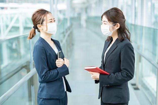 Asiatische geschäftsfrauen, die eine maske tragen und im geschäftsgebäude sprechen