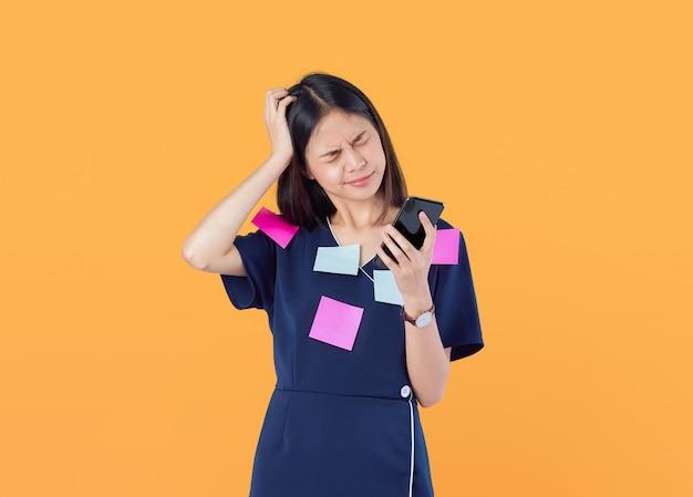 Asiatische geschäftsfrauen, die kopfschmerzen von der harten arbeit und vom starren entlang des smartphone für eine lange zeit, beitragsanmerkungen über den körper, auf orange glauben.