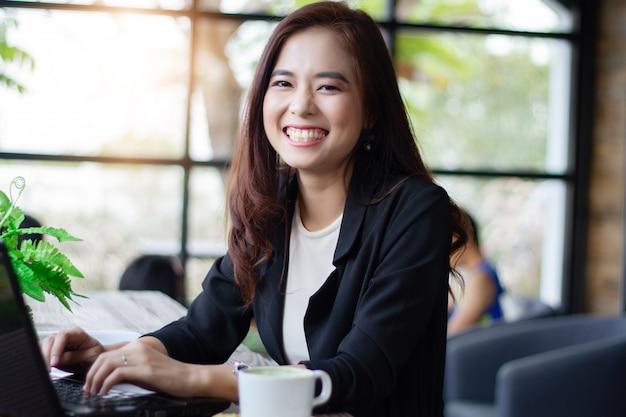 Asiatische geschäftsfrauen, die notizbuch für das arbeiten am kaffeecafé lächeln und verwenden
